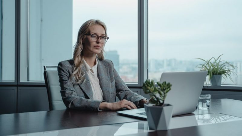 Woman sitting in front of computer on a desk.