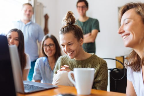 team member sitting in front of computer and smiling